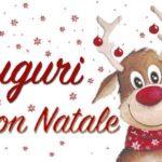 Nell'immagine: sfondo bianco con varie stelline rosse; al centro a sinistra scritta rossa su due righe, sopra Auguri e sotto Buon Natale; a destra disegno di una renna sorridente, con sciarpa rossa a stelle bianche, naso rosso e palline di natale rosse appese alle corna.